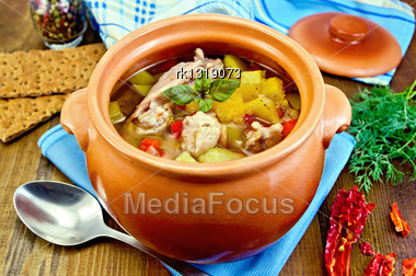 Roast With Chicken Meat, Potatoes And Red Pepper In A Clay Pot, Blue Napkin, Spoon, Crispbreads, Dill And Pepper In A Jar On The Board Stock Photo