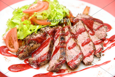 Roasted Beef Meat At Cranberries Sauce With Vegetables Stock Photo