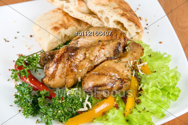 Roasted Chicken Drumstick Garnished With Fresh Green Salad, Pepper And Greens Stock Photo
