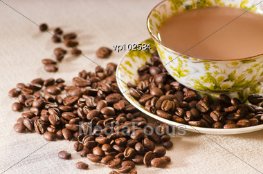 Roasted Coffee Beans And A Cup Full Of Coffee Stock Photo