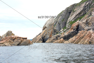 Rocks In The Blue Sea, Illuminated By The Sun. Background Stock Photo