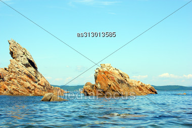 Rocks In The Blue Sea, Illuminated By The Sun. Background. Stock Photo