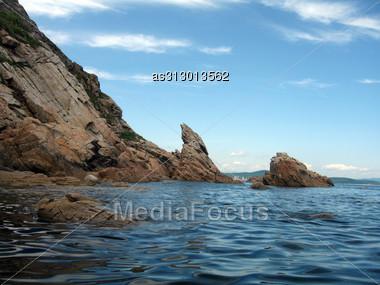 Rocks In The Blue Sea Background. Stock Photo
