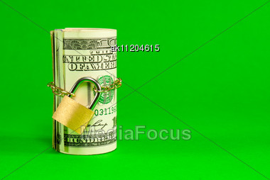 Roll Of US Dollars Chained And Locked Over Green Background Stock Photo