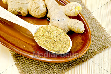 Roots Of Fresh Ginger, A Wooden Spoon With A Powder Of Ginger On Pottery On A Napkin On A Burlap Background Wooden Board Stock Photo
