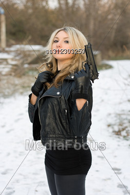Rough Armed Woman Holding A Gun In The Forest Stock Photo