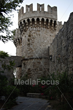 Round Stone Tower At Rhodes Castle With Trees And Flowers In Foreground Stock Photo