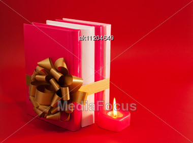 Row Of Books Tied Up With Ribbon And Burning Candle Over Red Background Stock Photo