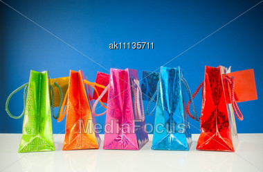 Row Of Colorful Bags Against Blue Background Stock Photo