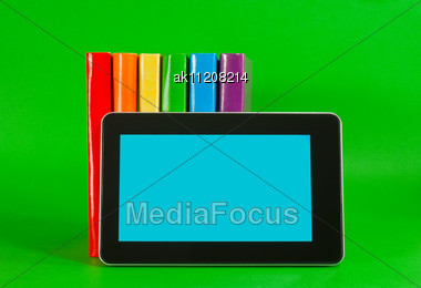 Row Of Colorful Books And Tablet PC Over Green Background Stock Photo