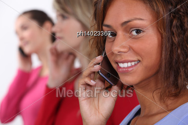 Row Of Women Talking On Their Cellphones Stock Photo