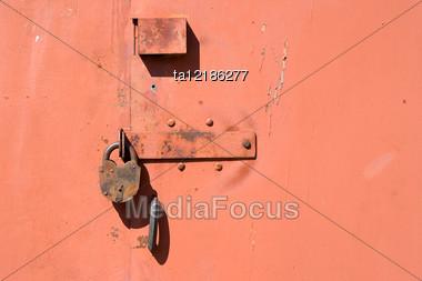Rusty Padlock On The Red Metal Door Stock Photo