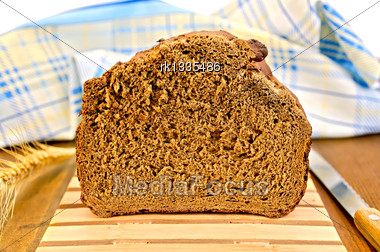 Rye Homemade Bread On A Wooden Stand, A Knife, Ear Of Rye, Blue Checkered Napkin On Wooden Board Stock Photo