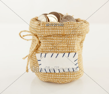 Sack Full Of Coins Against Light Background Stock Photo