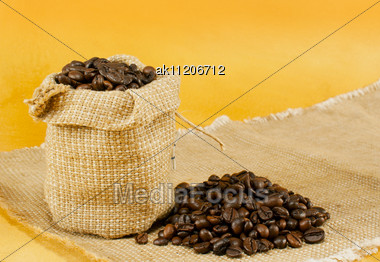 Sack With Roasted Coffee Beans Over Yellow Background Stock Photo