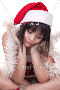 Sad Beautiful Girl Wearing Christmas Hat Sitting On The Floor And Thinking Of Something Stock Photo