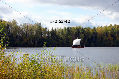 Sailing Boat On A Background Of A Forest And The Sky Stock Photo