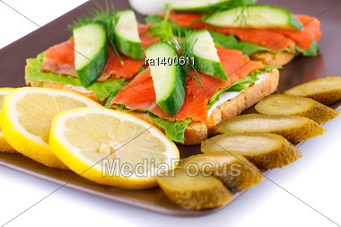 Salmon Sandwiches With Lettuce, Fresh And Pickled Cucumber, Onion, Lemon On Plate Isolated On White Background Stock Photo