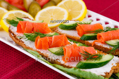 Salmon Sandwiches With Lettuce, Fresh And Pickled Cucumber, Onion, Lemon On Plate Stock Photo