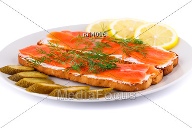 Salmon Sandwiches With Pickled Cucumber And Lemon On Plate Isolated On White Background Stock Photo