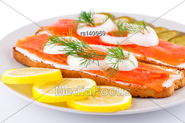 Salmon Sandwiches With Pickled Cucumber, Onion, Dill And Lemon On Plate Closeup Image Stock Photo