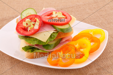 Sandwiches With Rusks, Vegetables, Bacon And Cheese On Plate Stock Photo