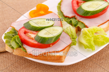 Sandwiches With Rusks, Vegetables, Bacon On Plate Stock Photo