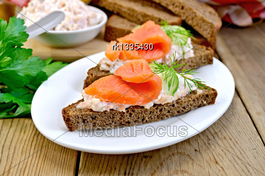 Sandwiches On Two Pieces Of Rye Bread With Cream, Dill, Cucumber And Salmon In A White Plate On A Wooden Boards Background Stock Photo