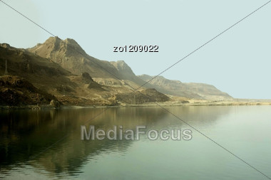 Sandy Mountains Are Reflected In Waters Of The Dead Sea Stock Photo