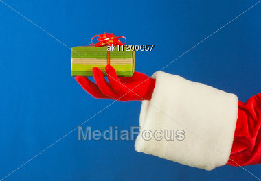 Santa's Hand Holding A Present Over Blue Background Stock Photo