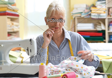 Seamstress At Sewing Machine Stock Photo