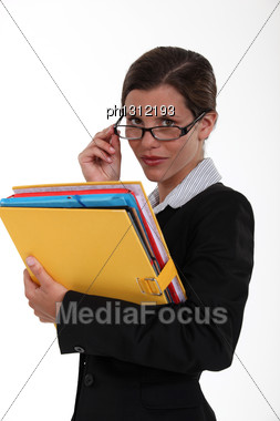 Secretary Holding A Binder And Peering Over Her Glasses Stock Photo