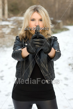 Seductive Girl Aiming With A Gun Against The Snow Stock Photo