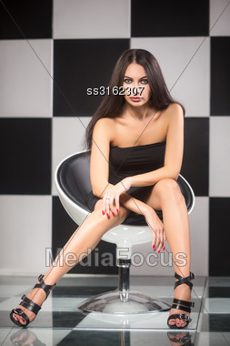 Seductive Young Brunette Posing On A Chair In The Studio Stock Photo