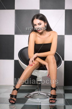 Seductive Young Brunette Posing On The Chair Stock Photo