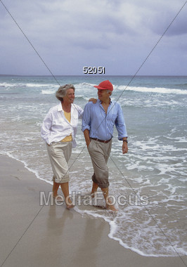 Senior Couple Barefoot on Beach Stock Photo
