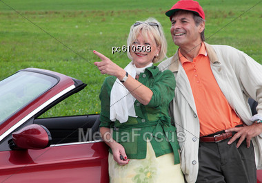 Senior Couple Leaning On Car Outside Stock Photo