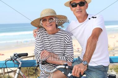 Senior Couple Riding Bikes By The Ocean Stock Photo