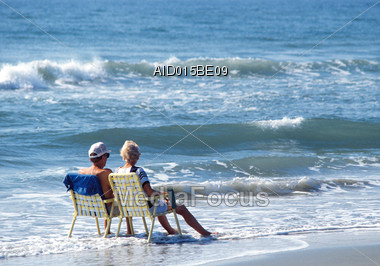 Senior Couple Sitting at the Beach Stock Photo
