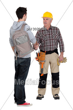 Senior Craftsman And Young Apprentice Shaking Hands Stock Photo