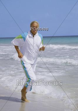 Senior Jogging Along Beach Stock Photo