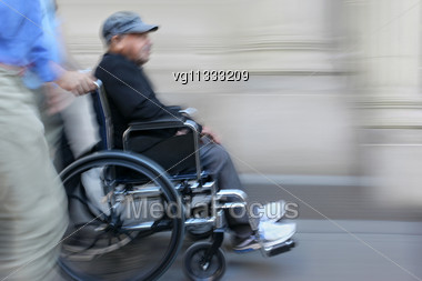 Senior Male Handicapped Person On A Wheelchair With Assistant In Motion Blur Stock Photo