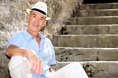 Senior Man Sitting On Some Old Stone Steps Stock Photo