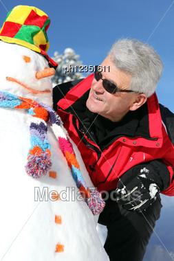 Senior Man With A Snowman Stock Photo