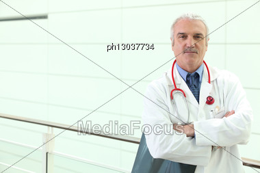 Senior Physician In Hospital Hall With Ex-rays Stock Photo