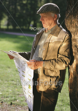 Senior Reading Newspaper in the Park Stock Photo