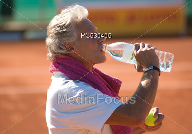 Senior Tennis Player Drinking Bottled Water Stock Photo