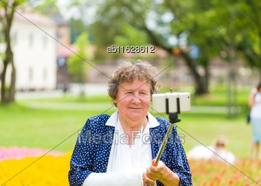 Senior Woman With Arm Splint Taking Selfie Holding Smartphone On Stick In The Garden Stock Photo