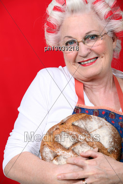 Senior Woman With Curlers In Her Hair Holding Fresh Baked Bread Stock Photo