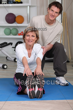 Senior Woman Doing Floor Exercises With A Coach Stock Photo